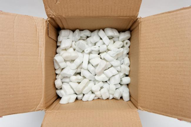 A cardboard box with packing foam pellets top view