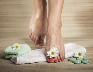 Female feet with drops of water, towel, flowers and spa rocks.