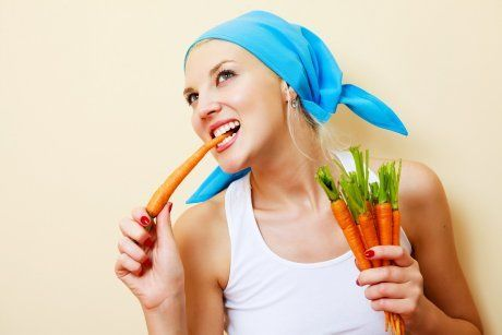 Женщина ест морковку