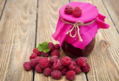 Raspberry jam with fresh raspberries on wooden background