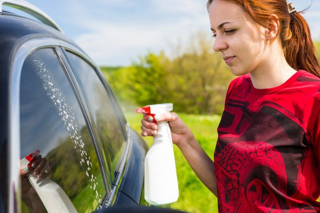 Woman Wearing Red Shirt Cleaning Car Windows with Spray Bottle Cleaner in Green Field on Bright Sunny Day