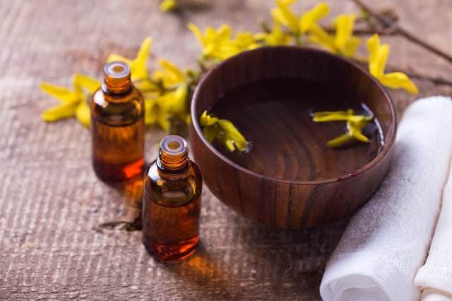 Spa setting. Essential aroma oil , water in bowl, towels, yellow flowers on aged wooden background. Selective focus.