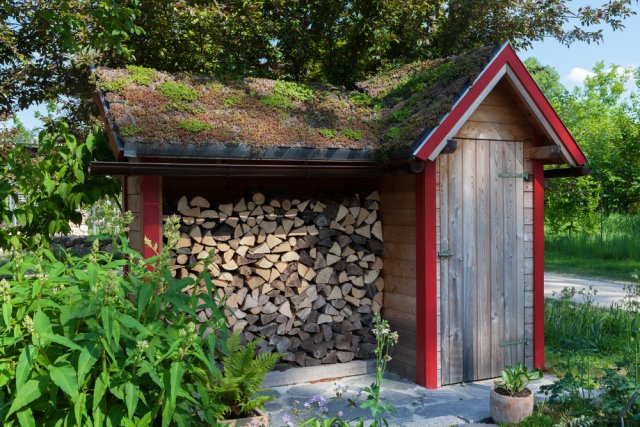 Small hut in the garden with firewood