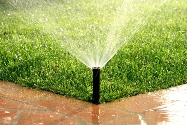 разбрызгиватель поливает траву