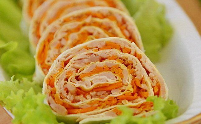 Рулет с ветчиной, сыром и корейской морковью закуска на тарелке ролл фото