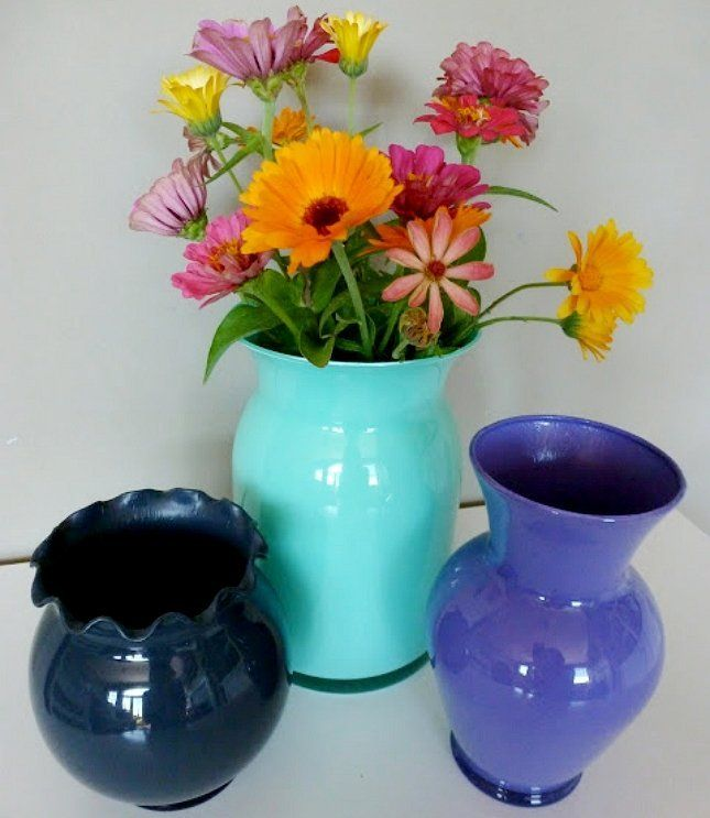 Даже если вазы не слишком сочетаются между собой, объединить их в общую композицию смогут одинаковые цветы